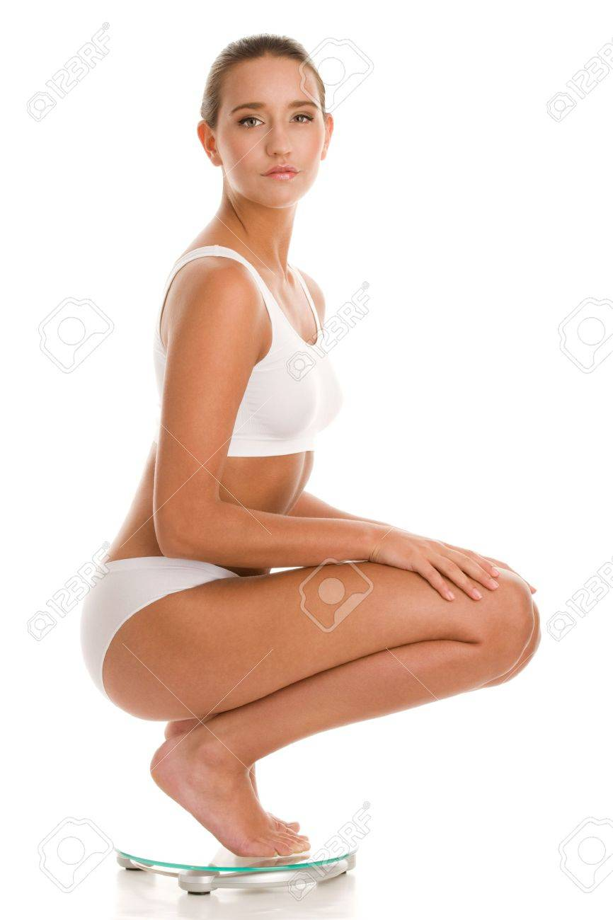 Young woman crouching on bathroom scale Stock Photo - 9455272