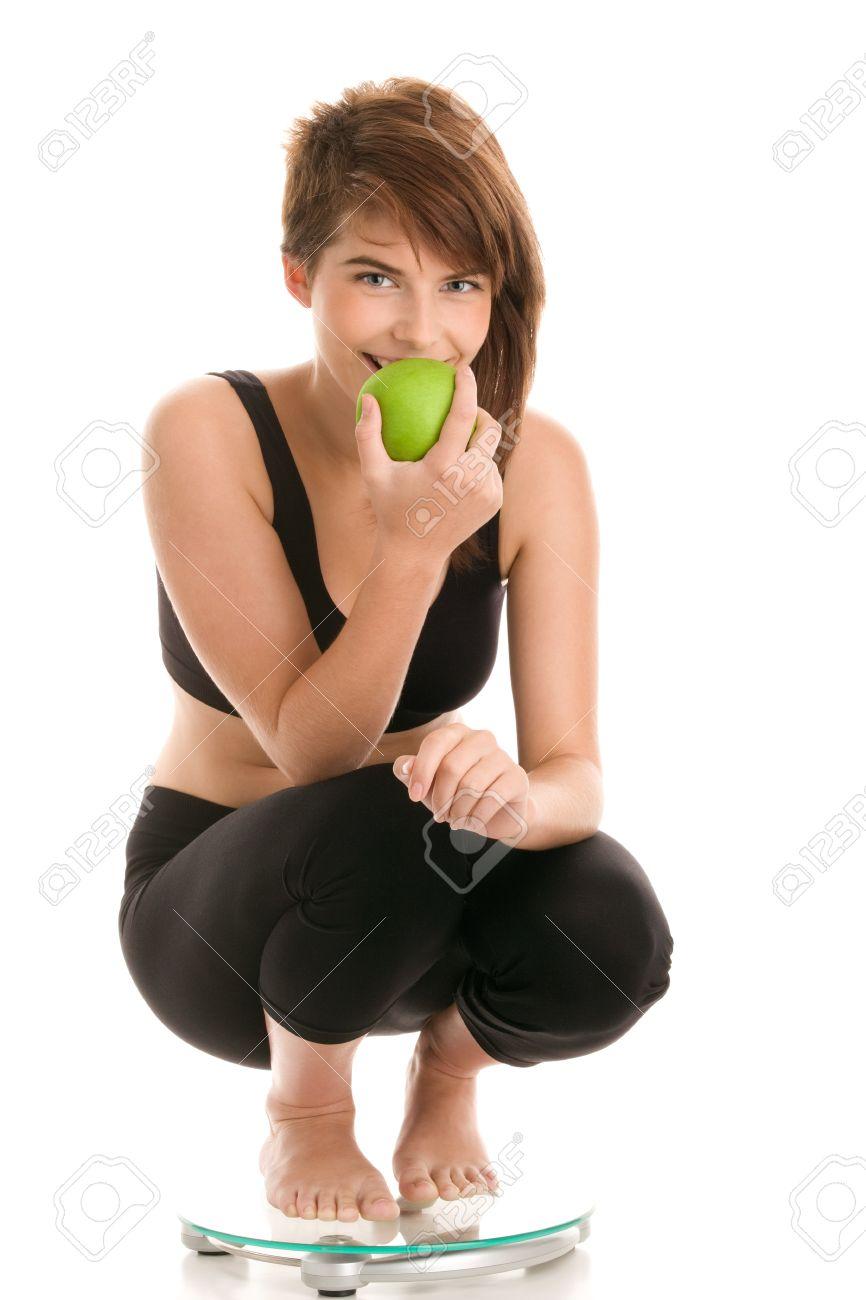 Junge Frau Hockend Auf Badezimmer Skala Essen Apple Lizenzfreie Bilder    9455296