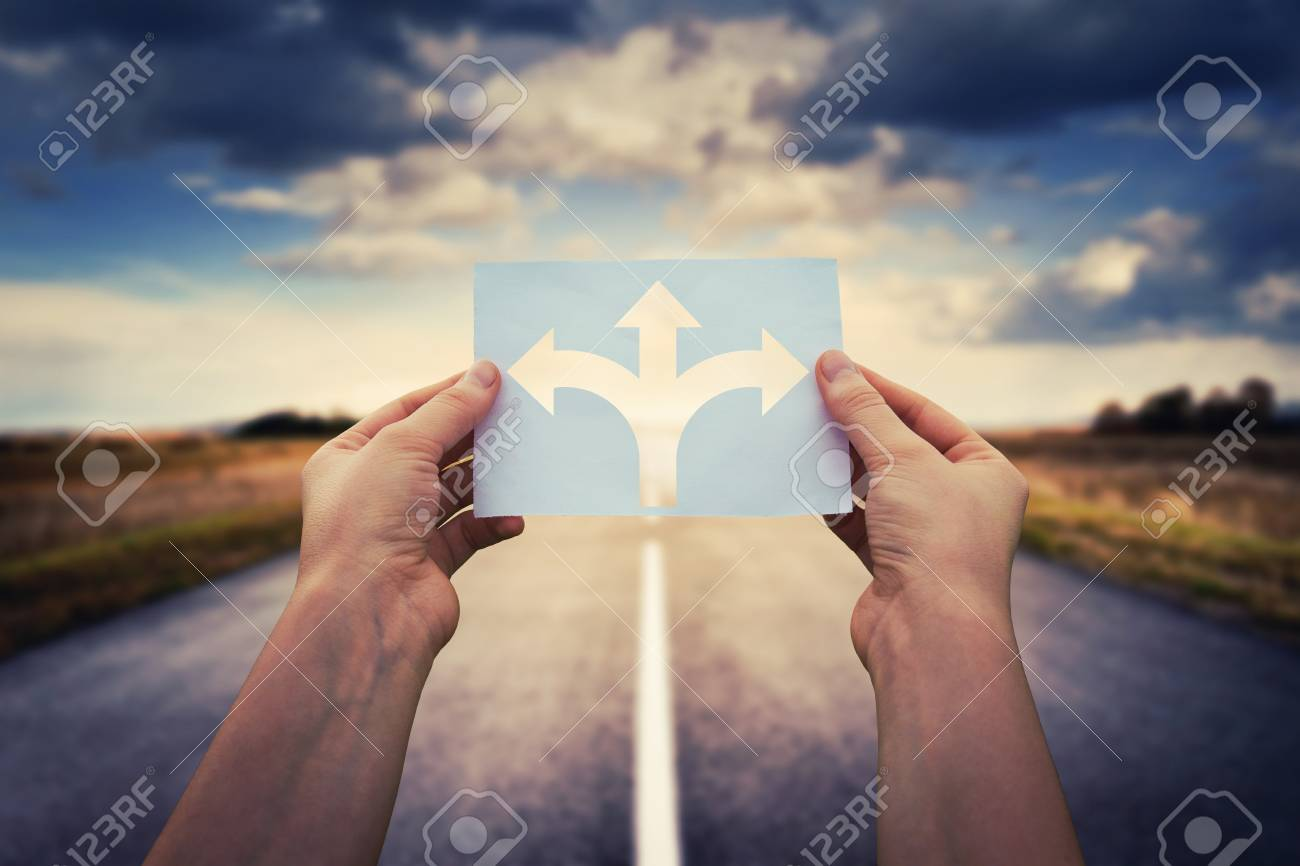Hands holding paper with arrows crossroad symbol splitted in three different directions. Choose the correct way between left, right and front. Difficult decision concept, over asphalt road background. - 115946611