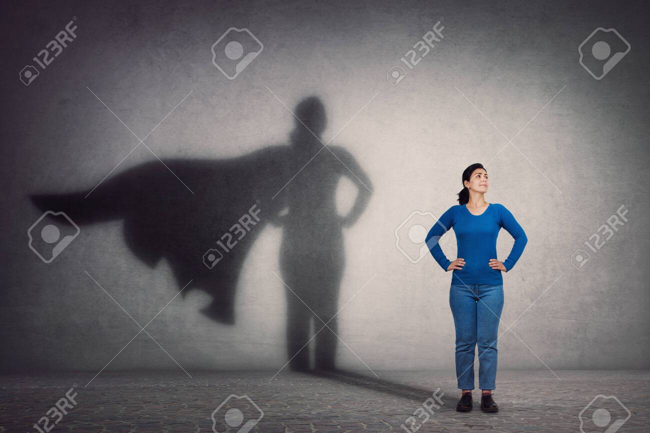 Brave woman keeps arms on hips, smiling confident, casting a superhero with cape shadow on the wall. Ambition and business success concept. Leadership hero power, motivation and inner strength symbol. - 133633547