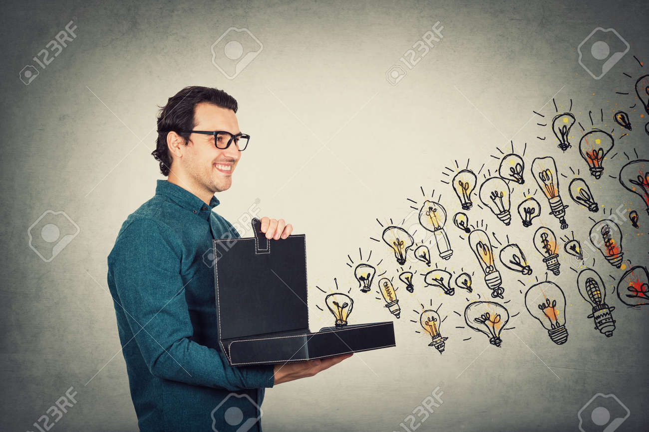 Businessman opens his briefcase filled with brilliant ideas as different lightbulbs comes out of the box. Ingenious boss shows the business portfolio, shares his creativity and genius with employees. - 154953363