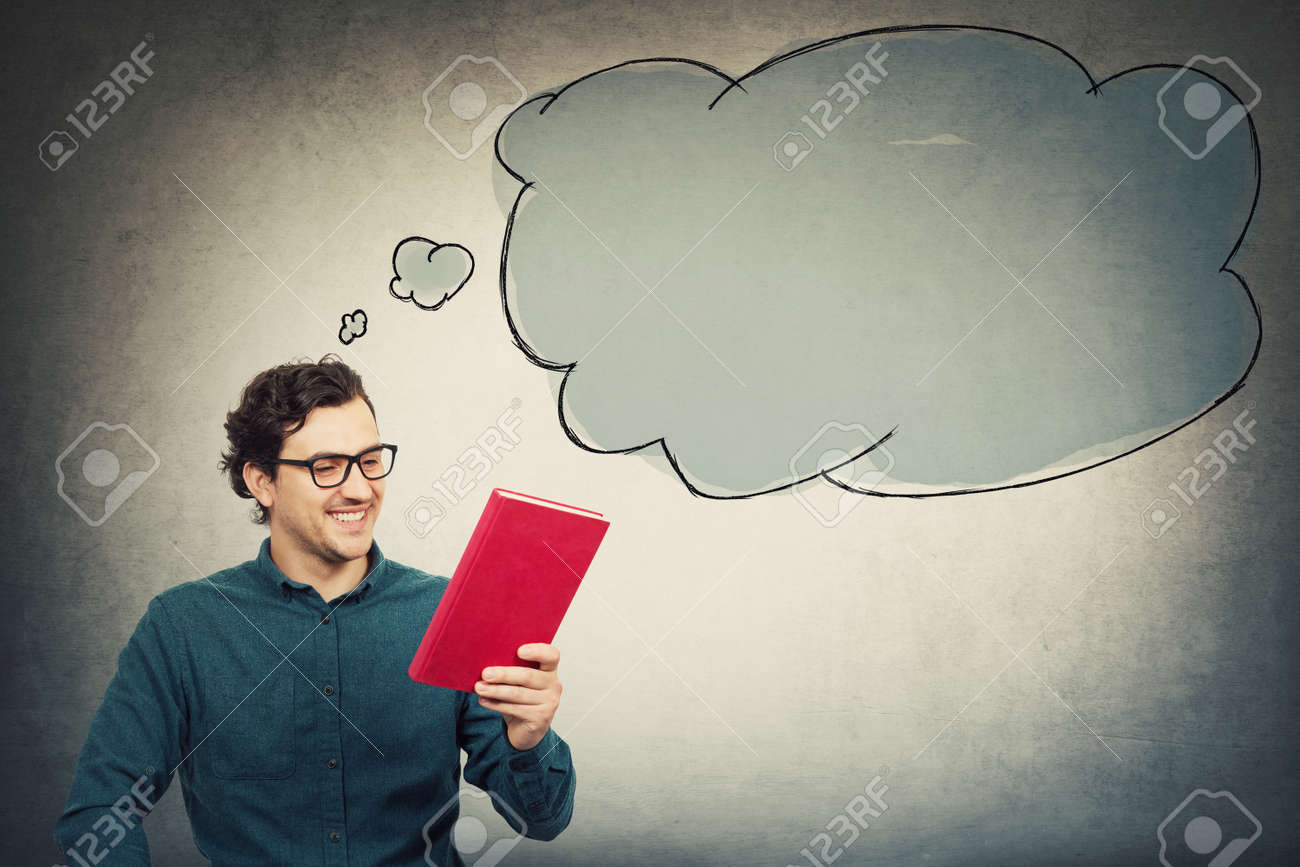 Happy young man, student guy, holding an interesting red book, reading the textbook title. Education concept, learning process. Guy choose what to read. Empty thought bubble comes out of his head. - 153438424