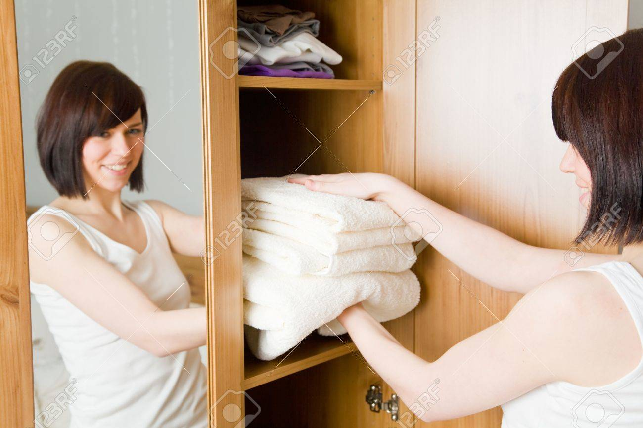 Young woman with white towels in her wardrobe Stock Photo - 4824255
