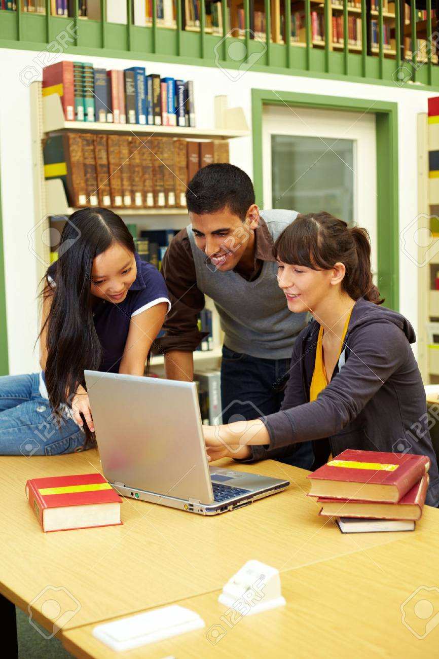Three happy students learning in university library Stock Photo - 5931983