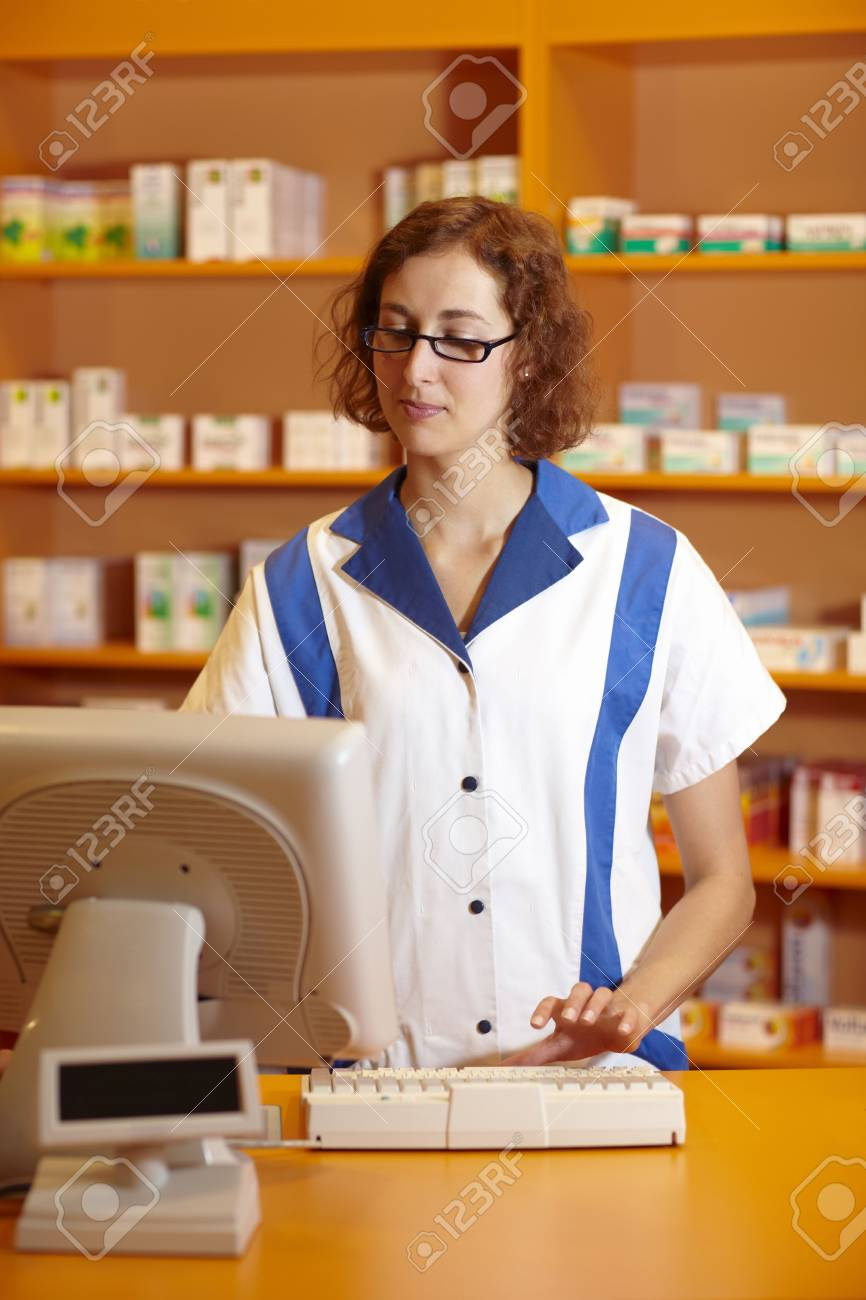 Pharmacist typing on computer behind pharmacy counter Stock Photo - 6053487