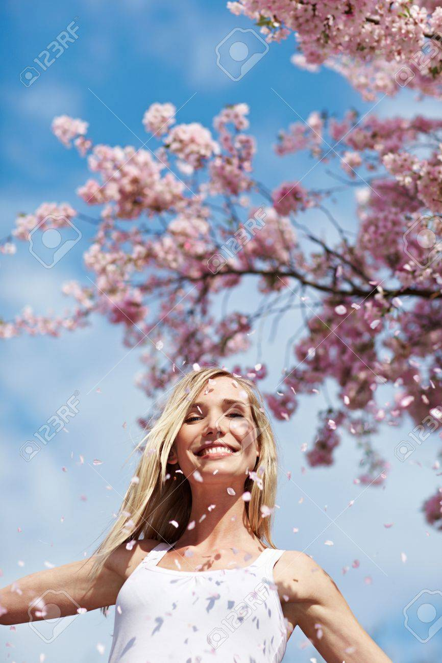 Young woman throwing pink cherry blossoms in the air - 6857964