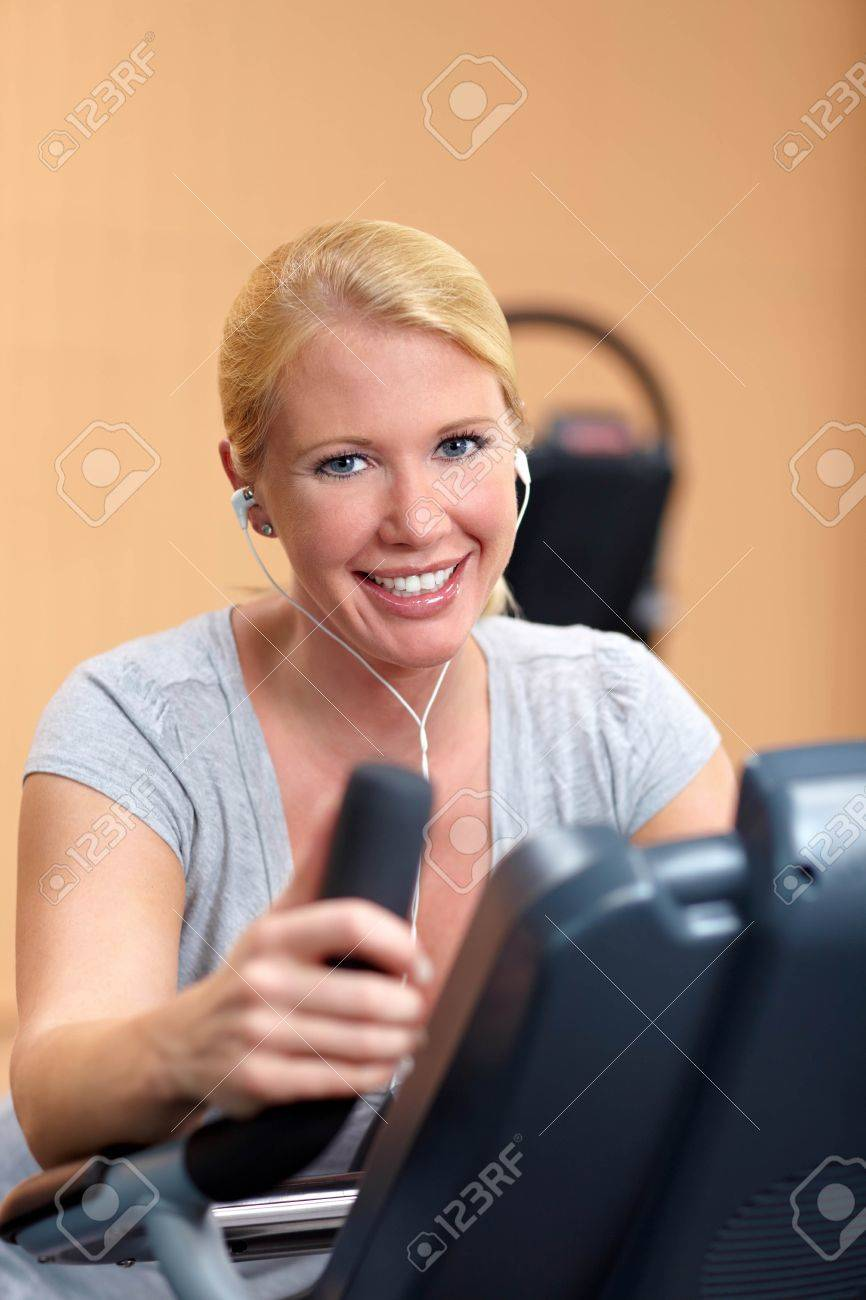 Happy woman in gym on a hometrainer listening to music Stock Photo - 7940571