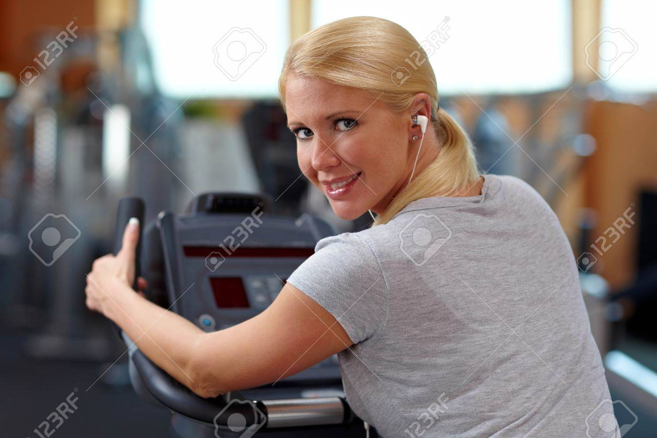 Happy woman in gym on a hometrainer listening to music Stock Photo - 7940578
