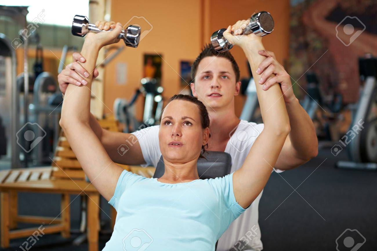 Woman doing weight training with fitness coach Stock Photo - 8128581
