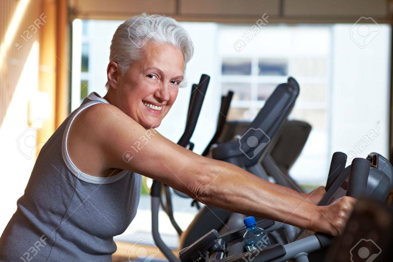 Happy senior woman exercising on spinning bike in gym Stock Photo - 8128434