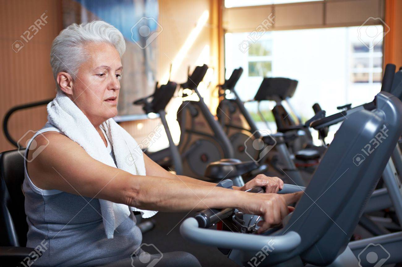 Senior woman with grey hair on home trainer in gym Stock Photo - 8209749