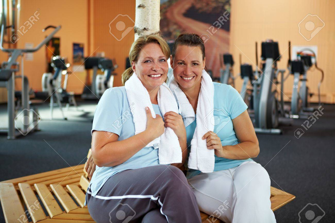Two happy women talking after their fitness training in gym Stock Photo - 8209837