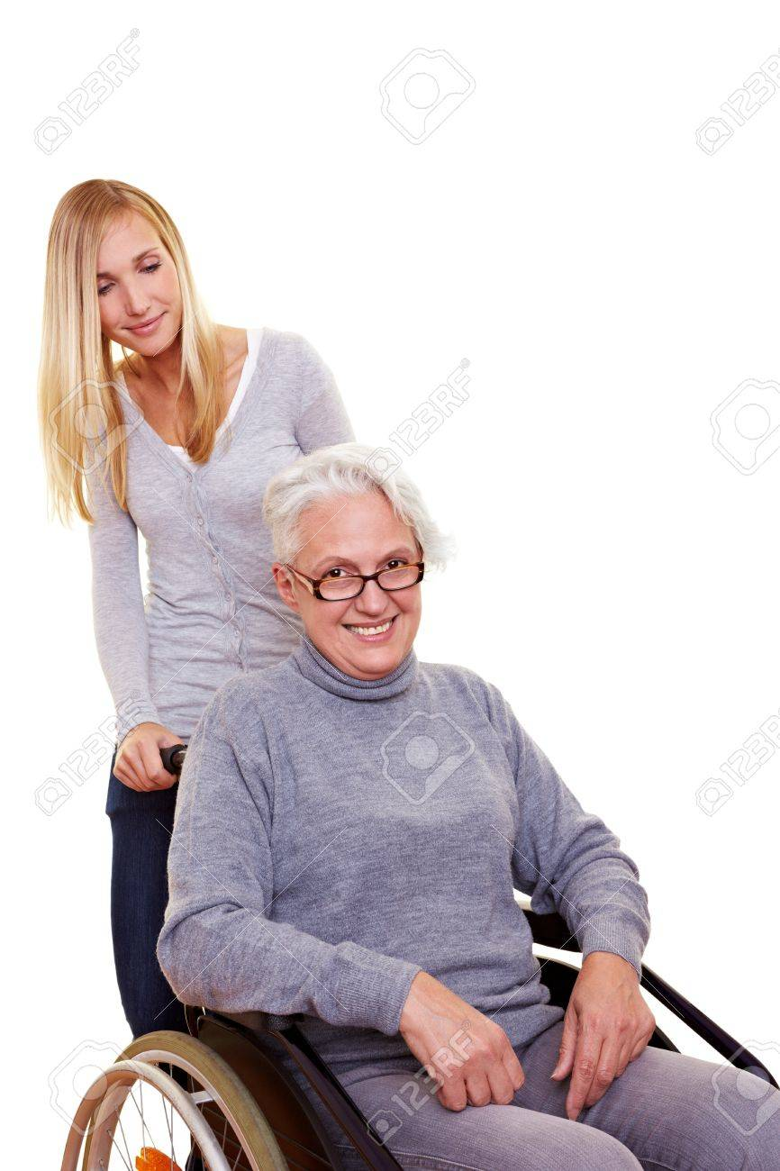 Granddaughter driving her happy grandmother in wheelchair Stock Photo - 8287010