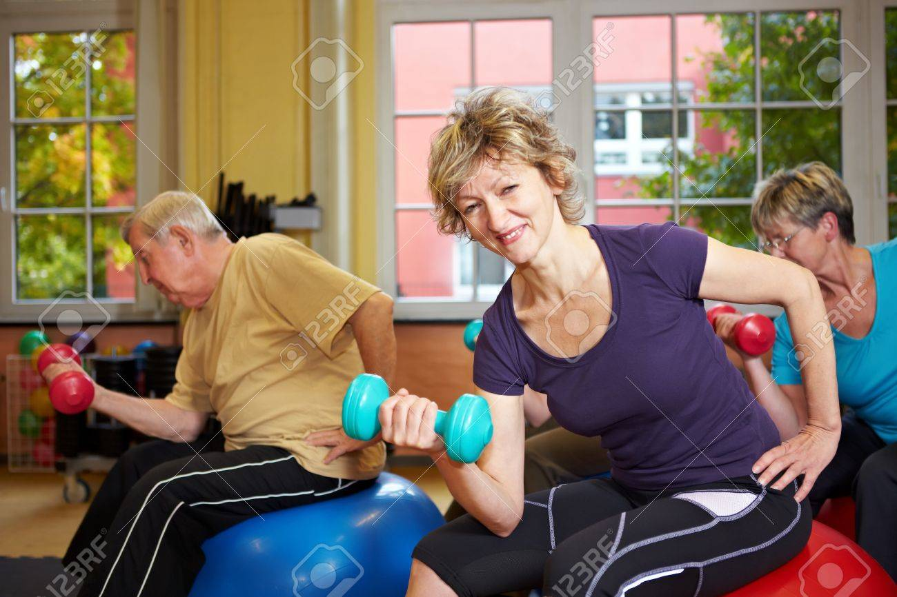 Mixed group doing dumbbell exercises in a gym Stock Photo - 8347349