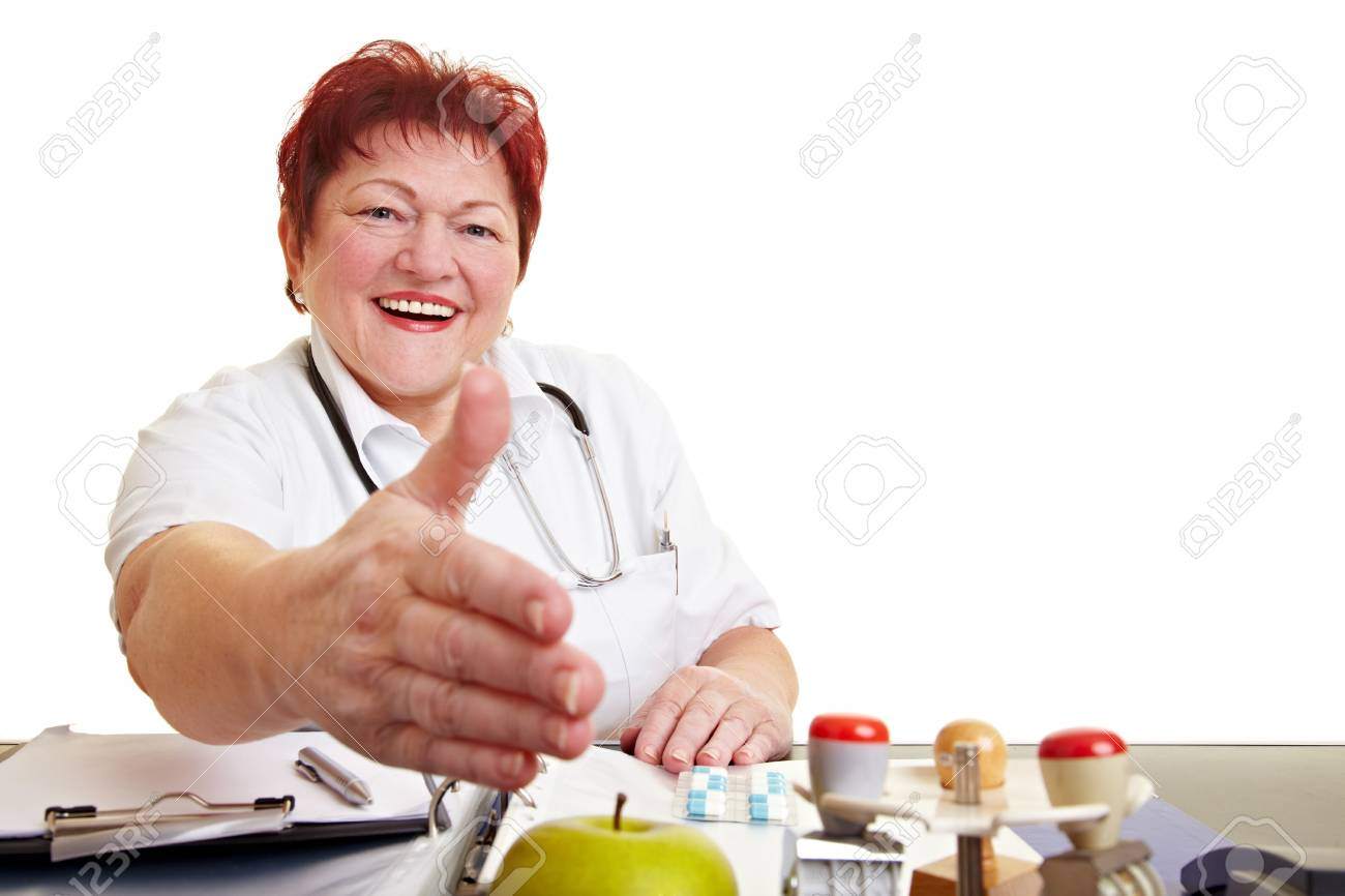 Female doctor sitting at desk offering a handshake Stock Photo - 8621352