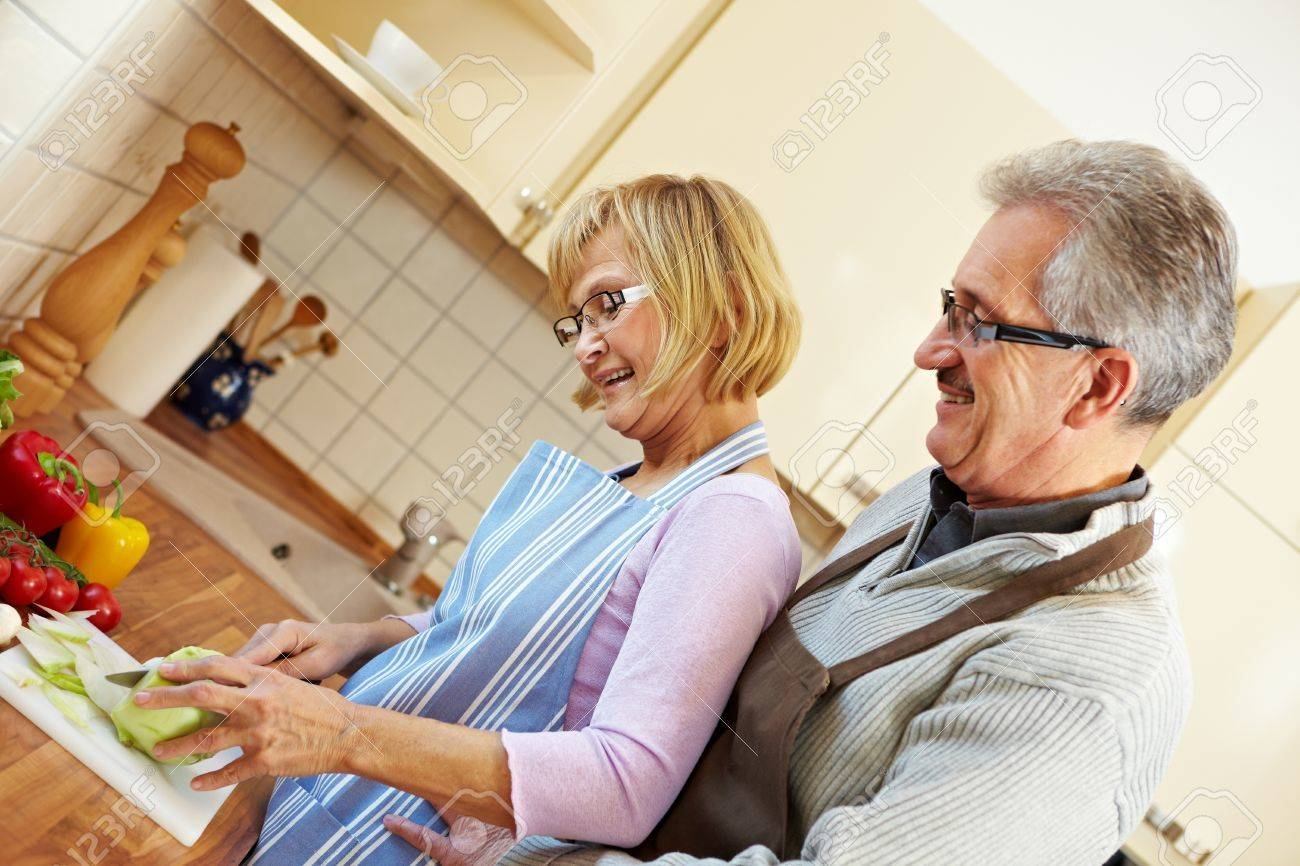Elderly husband watching his wife cutting vegetables in the kitchen Stock Photo - 8903572