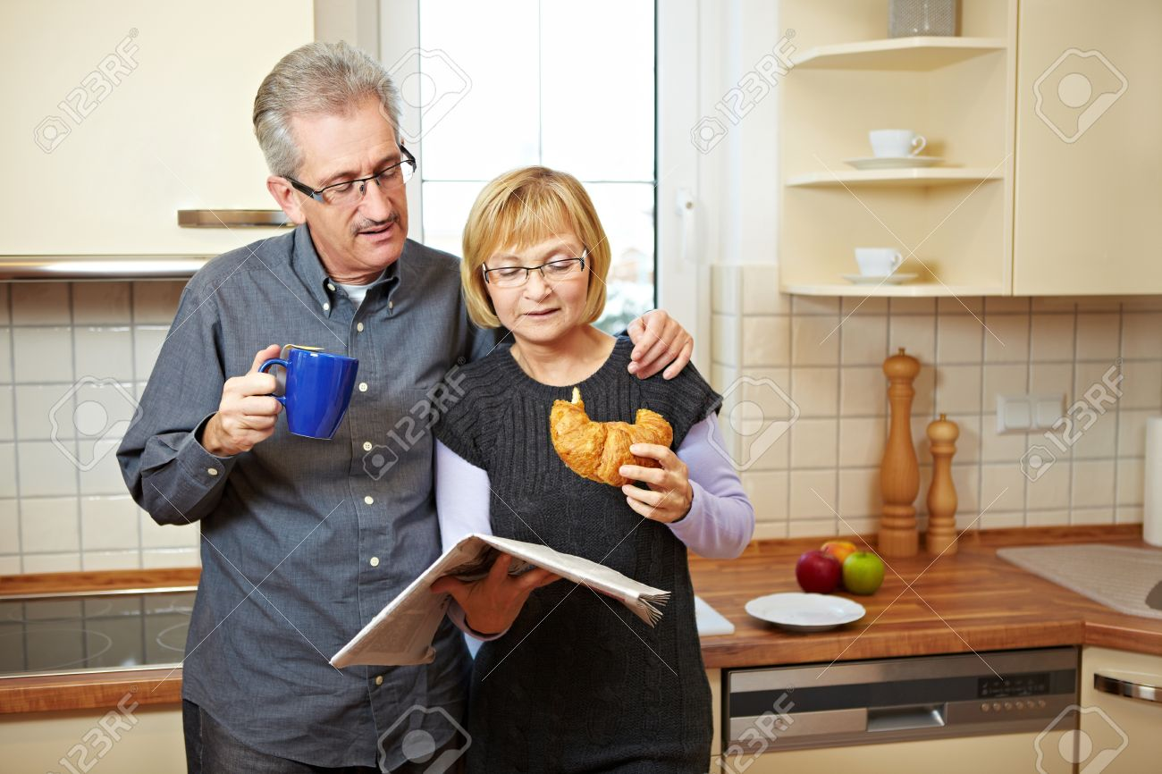 Senior couple reading newspaper while eating breakfast in the kitchen Stock Photo - 8903616