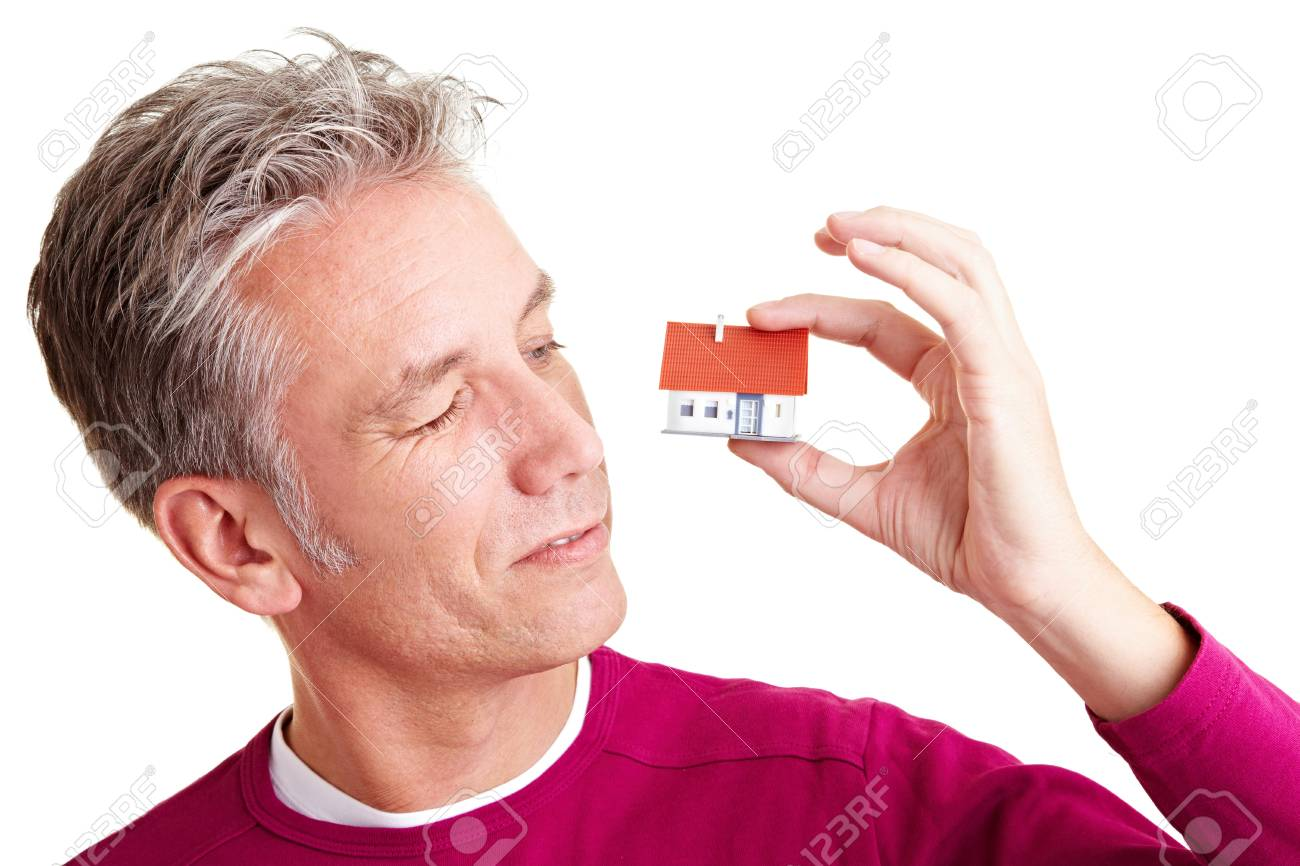 Senior man looking at a small miniature house Stock Photo - 8953293