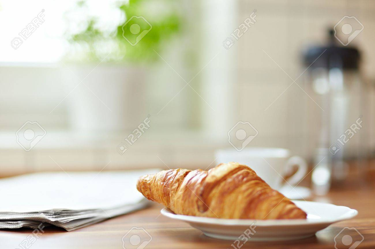 Croissant with newspaper and a cup of coffee on a kitchen counter Stock Photo - 8988435