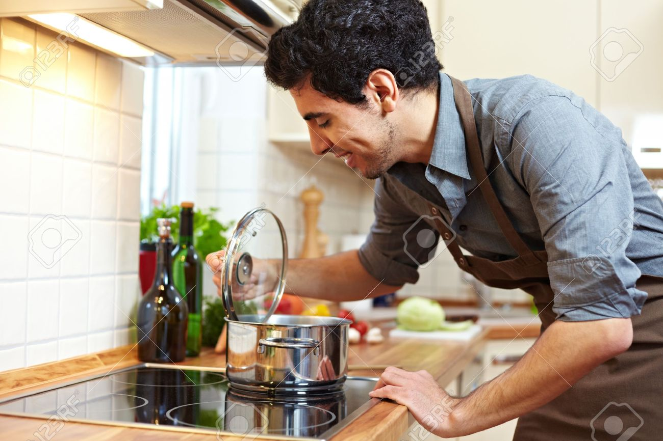Man Watching A Pot On A Stove In The Kitchen Stock Photo