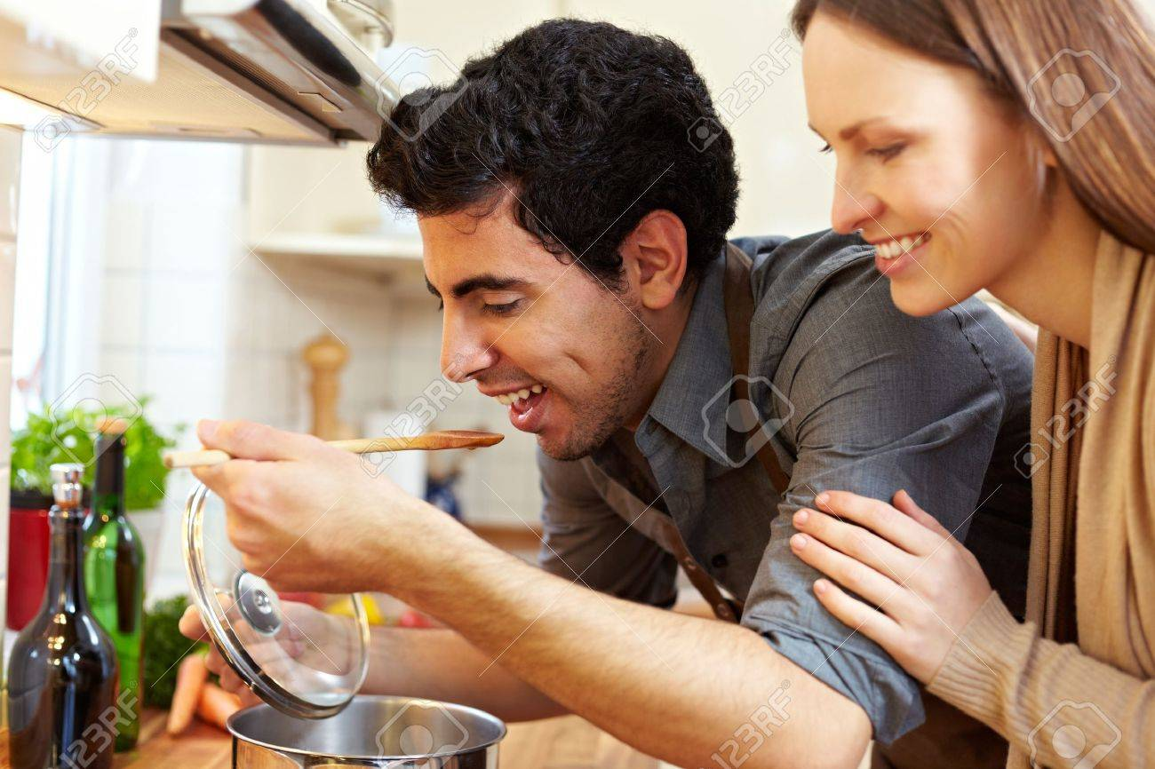 Man tasting soup on a stove in kitchen while happy woman is watching Stock Photo - 8988485