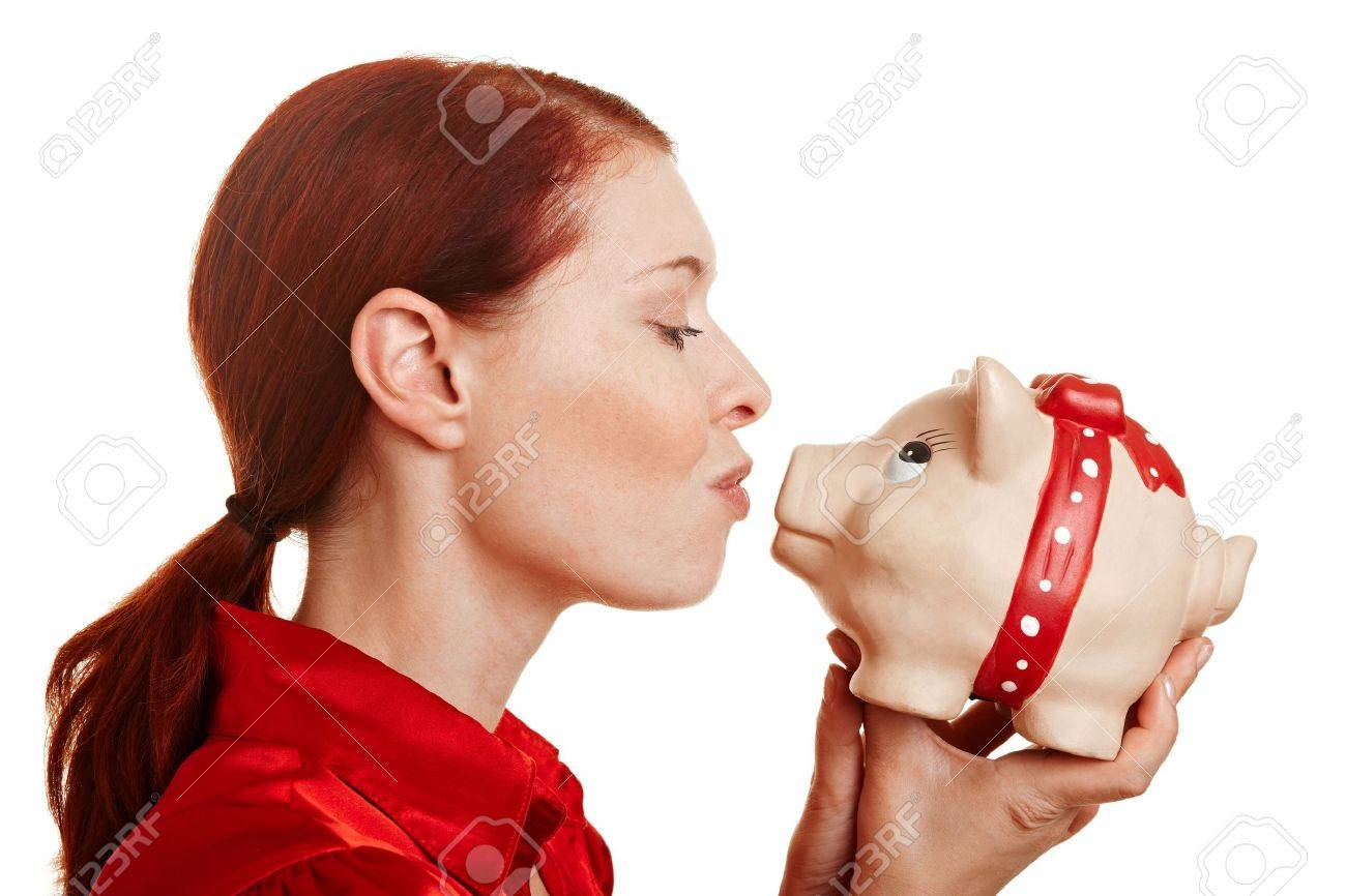 Redhaired woman kissing a big piggy bank Stock Photo - 10483043