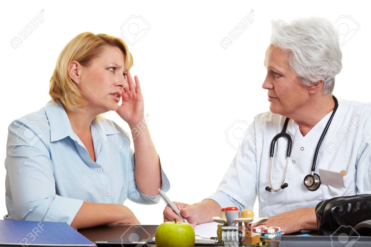 Woman with migraine at an elderly doctor Stock Photo - 10560397