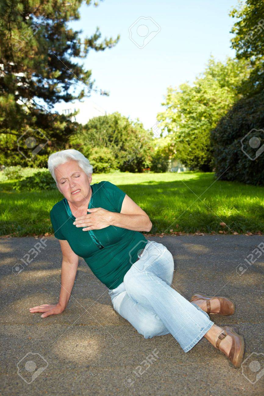 Senior woman with heart pain sitting in a park Stock Photo - 10585672