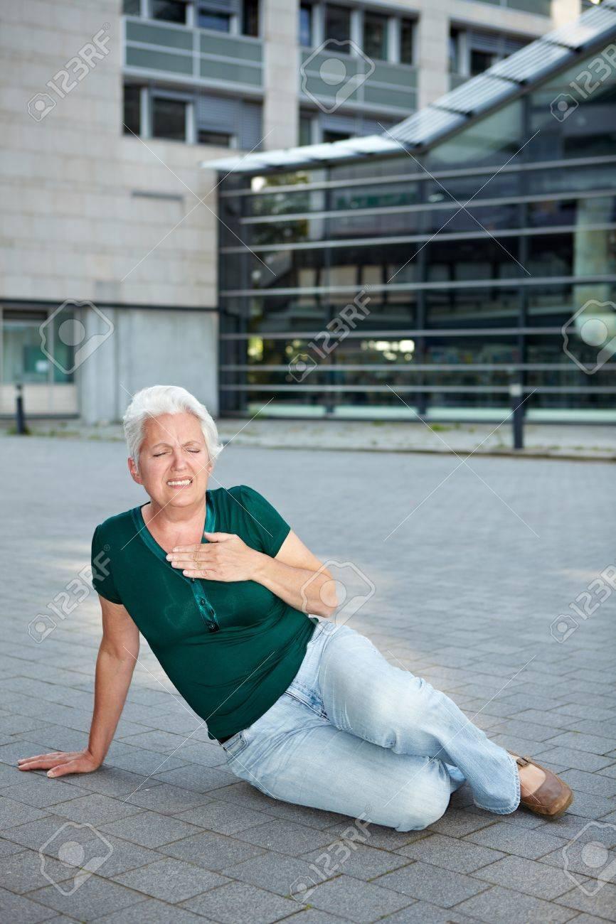 Senior woman with heart attack sitting on sidewalk Stock Photo - 10651750