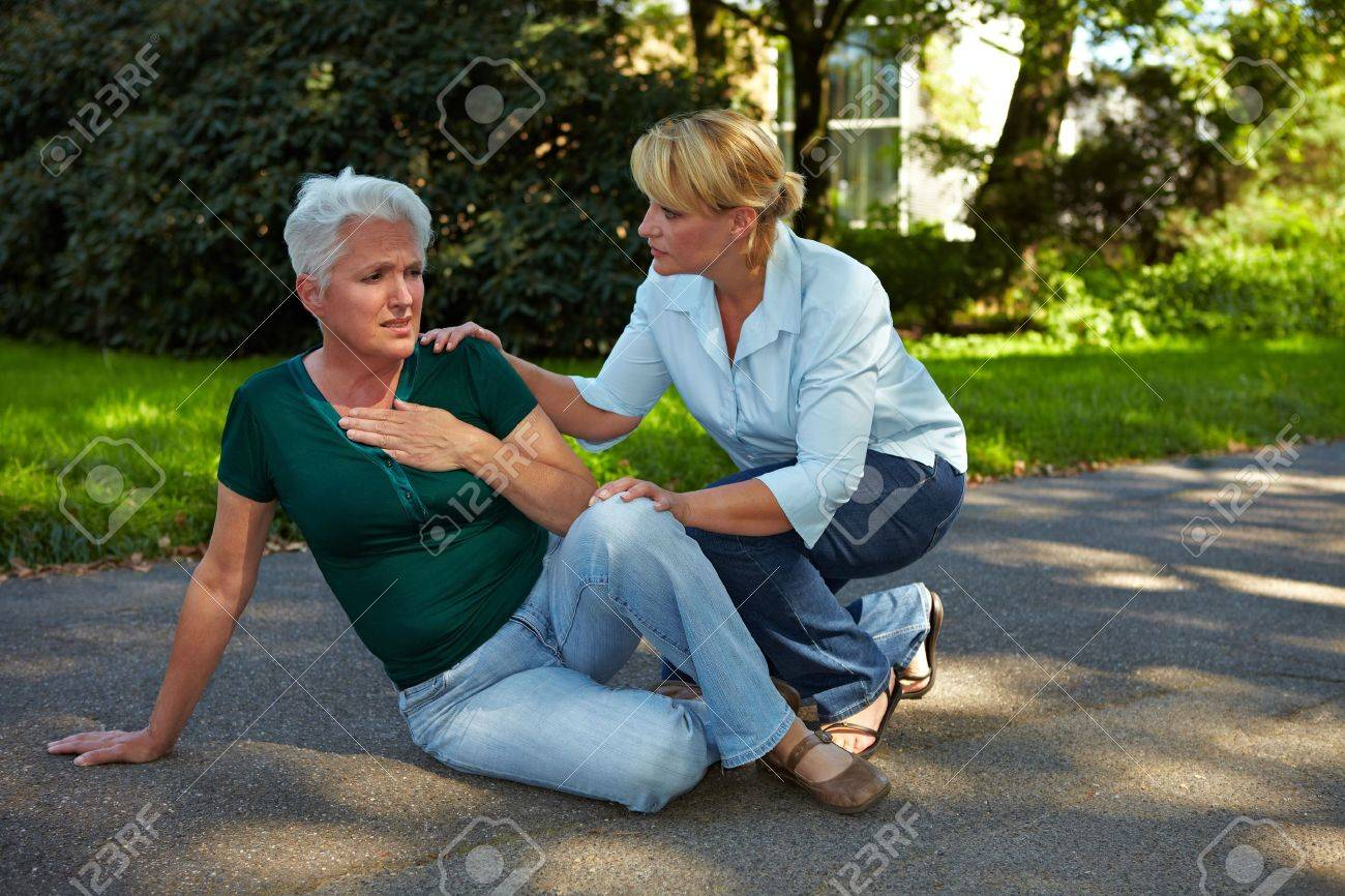 Passerby helping senior woman with heart attack in park Stock Photo - 10651755