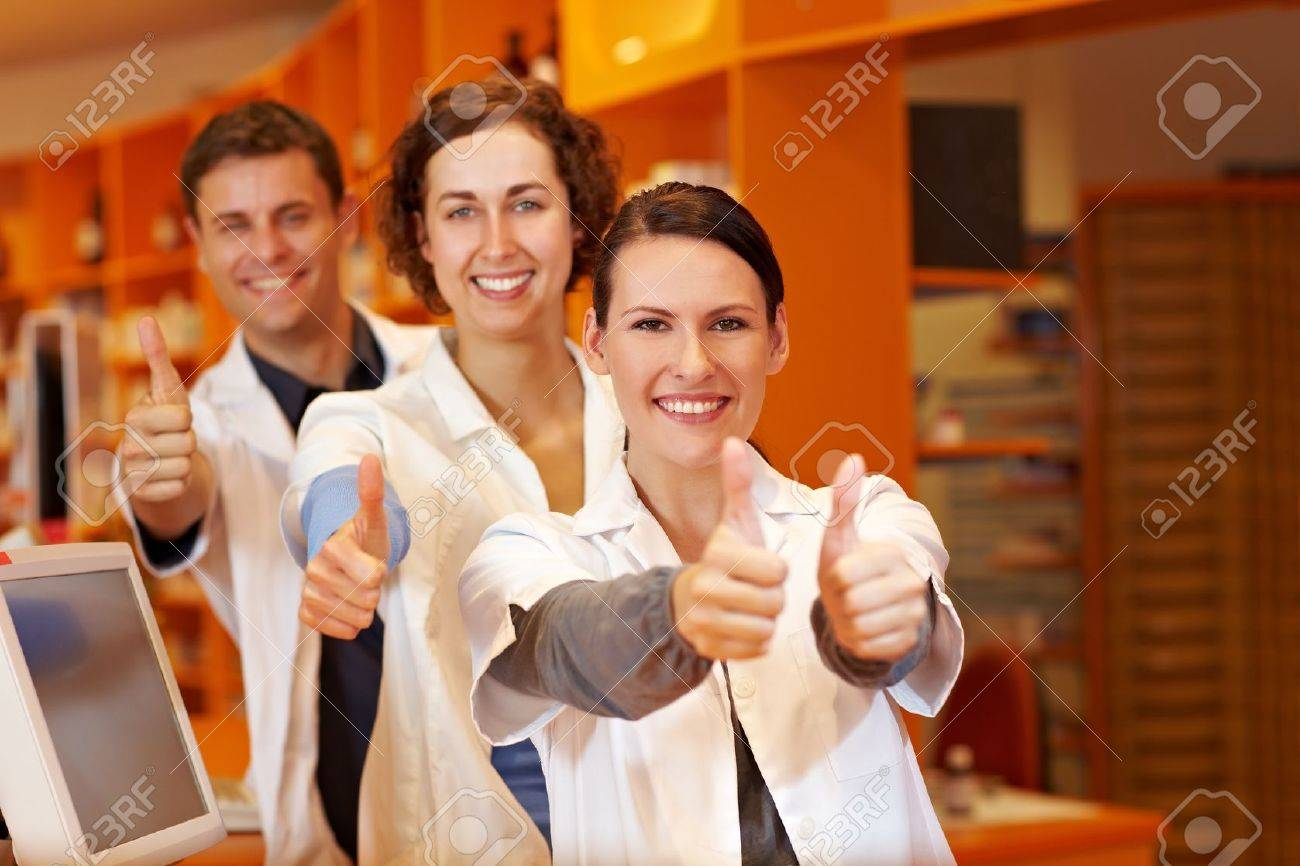 Three happy pharmacists holding their thumbs up in pharmacy Stock Photo - 11031483