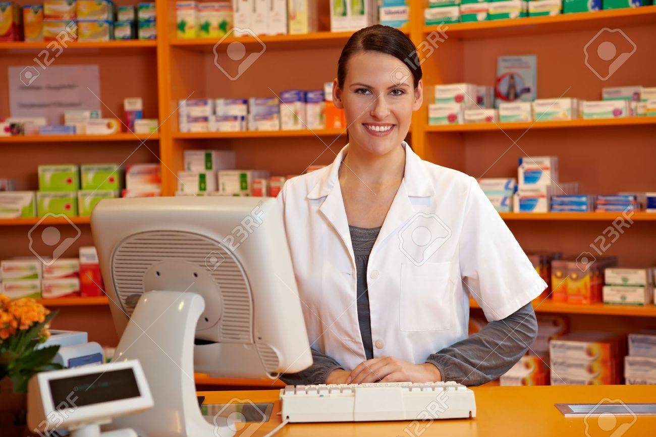 Happy pharmacist standing at checkout counter in a drugstore Stock Photo - 11031347