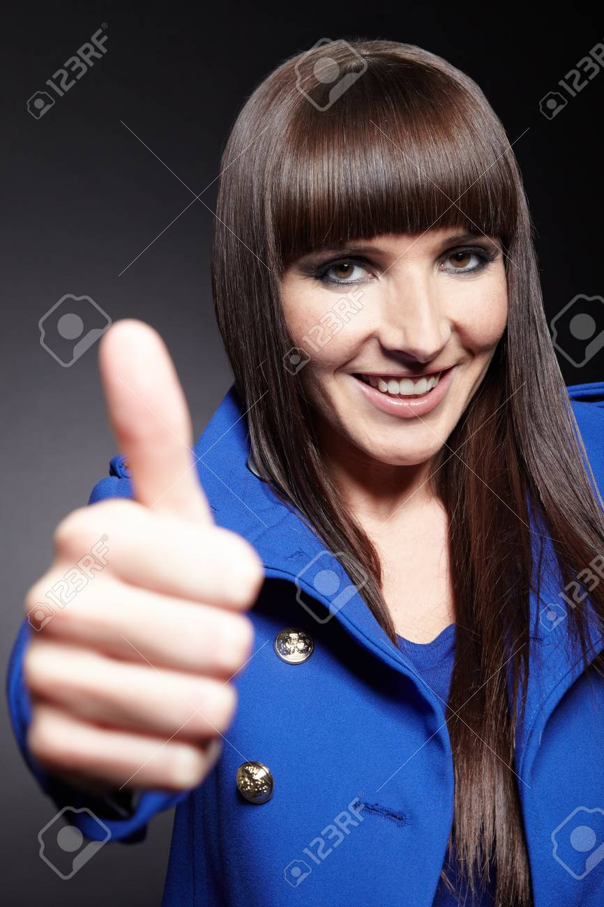 Young happy woman in blue coat holding her thumbs up Stock Photo - 11396223
