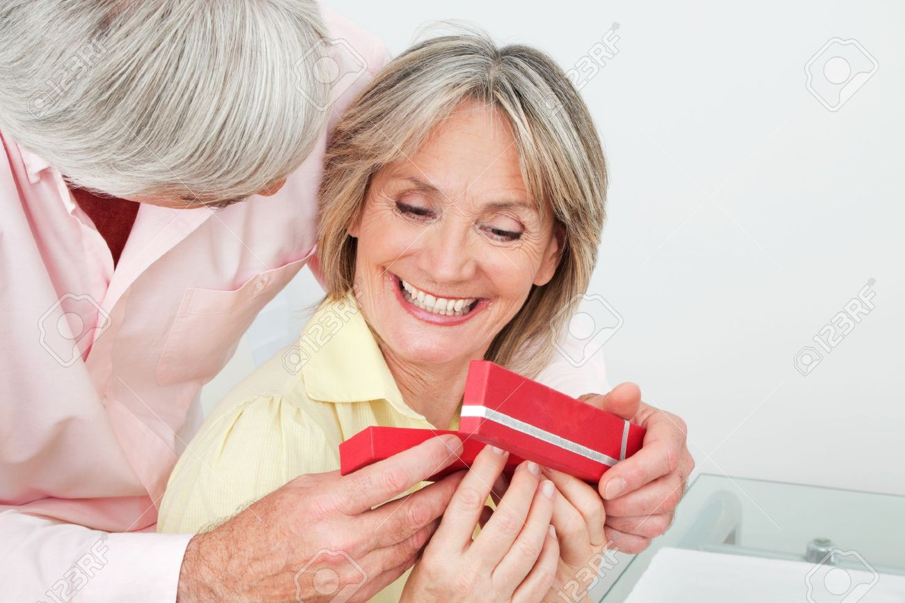 Happy smiling senior woman receiving gift from her husband Stock Photo - 12361619