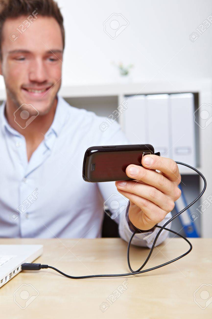 Young business man downloading images from cell phone to computer via USB Stock Photo - 12361590