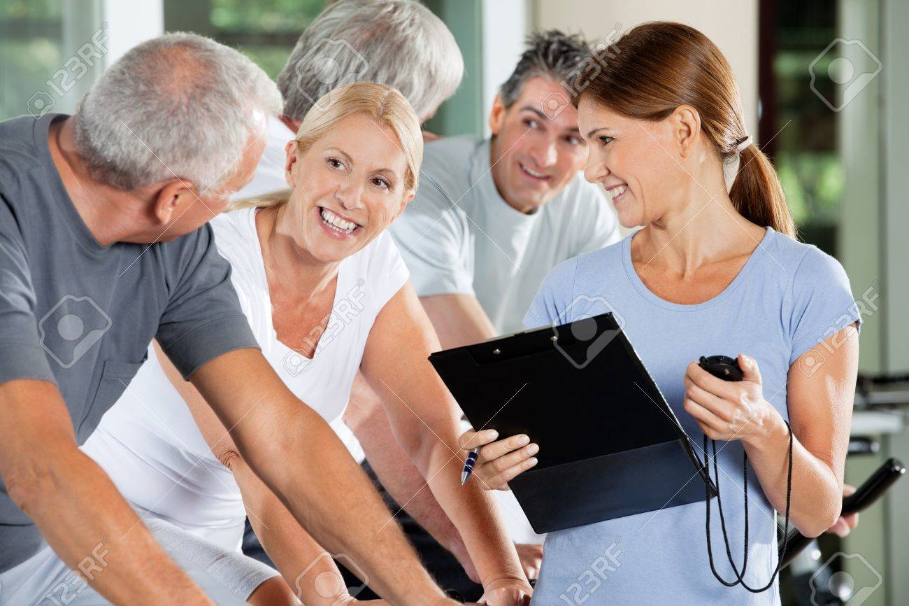 Happy seniors with fitness trainer in a gym Stock Photo - 12954413