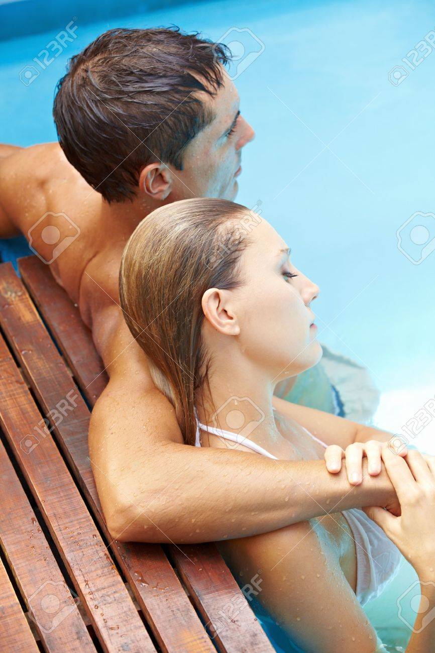 Attractive young couple relaxing together in swimming pool with blue water Stock Photo - 13560646