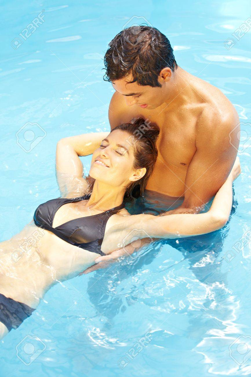 Young attractive couple relaxing together in blue swimming pool Stock Photo - 13560517