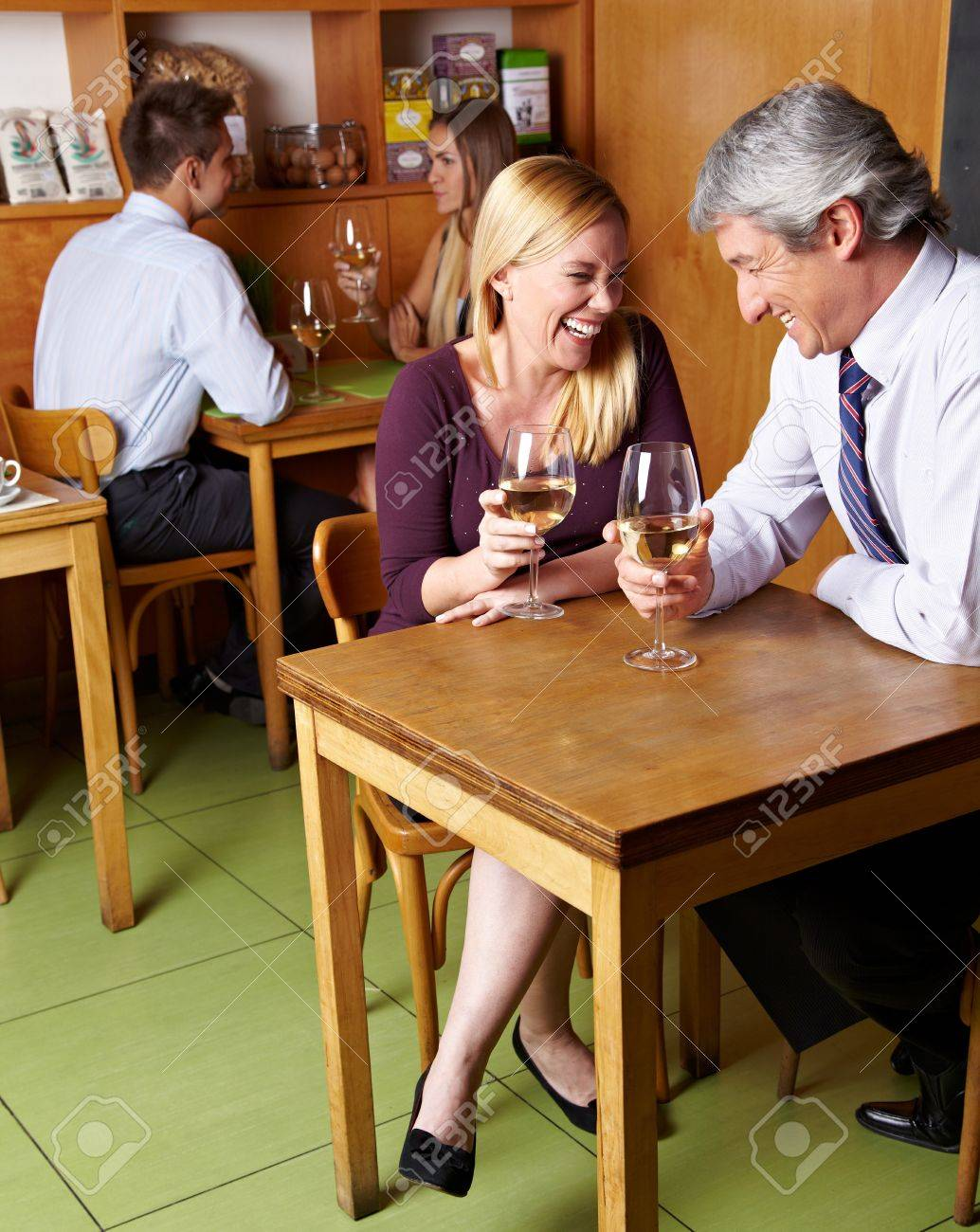 Two happy laughing senior people drinking white wine in restaurant Stock Photo - 14428700
