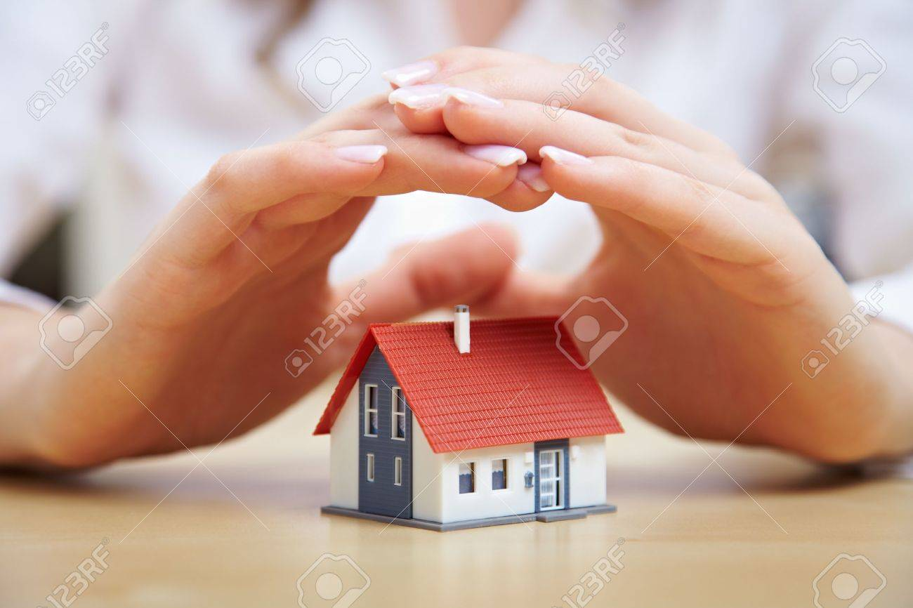 Female hands saving small house with a roof Stock Photo - 14639840