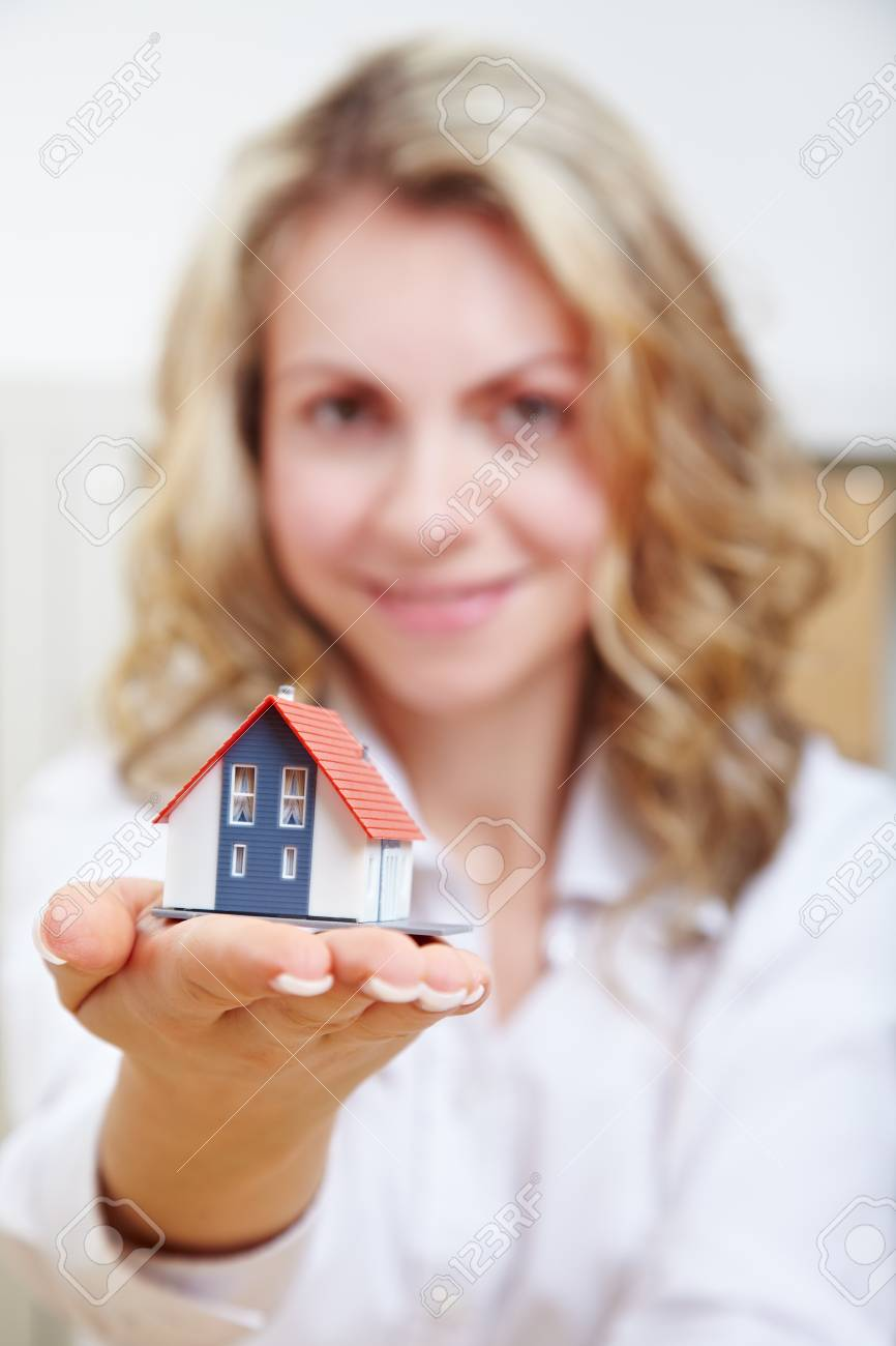 Happy attractive woman with small house on her hand Stock Photo - 14639829