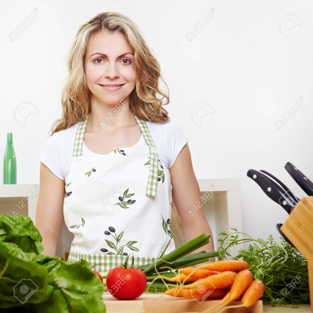 Attractive smiling woman standing in kitchen with vegetables behind chopping board Stock Photo - 14754697