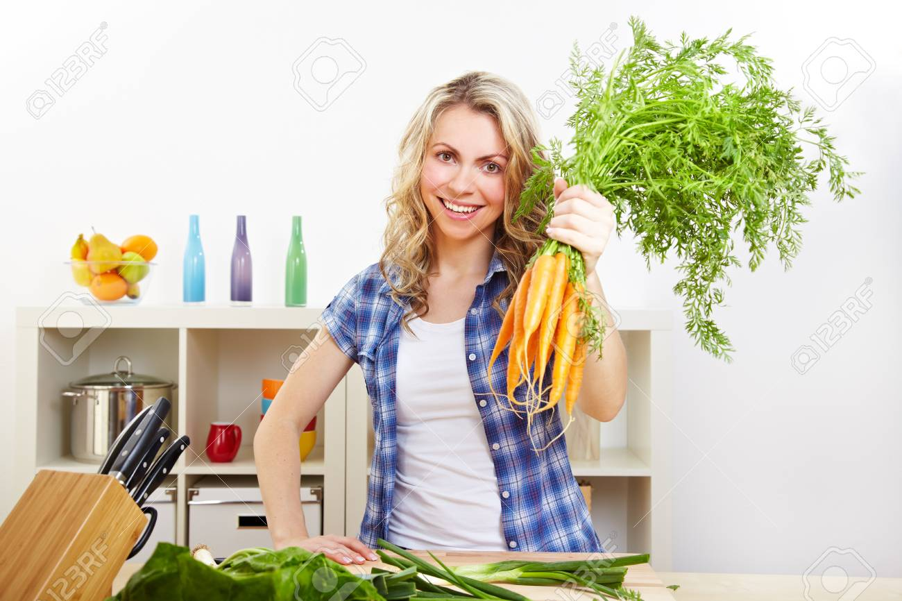 Happy attractive woman with bunch of carrots in the kitchen Stock Photo - 14736696
