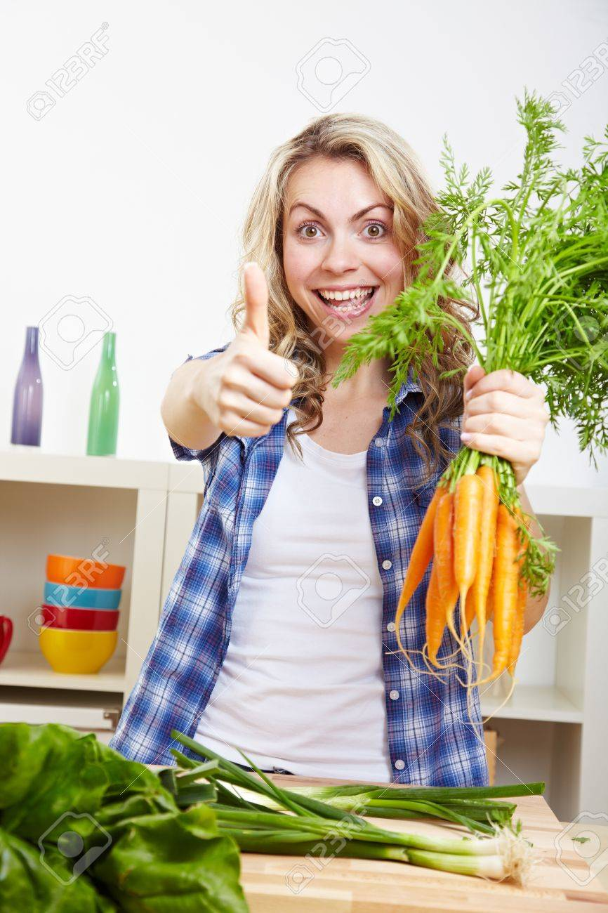 Young happy woman with vegetables in kitchen holding her thumbs up Stock Photo - 14754574