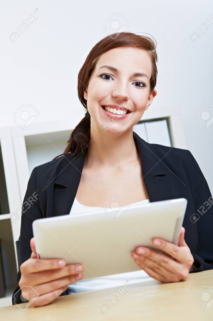 Smiling businesswoman sitting with her tablet pc in an office Stock Photo - 14903265