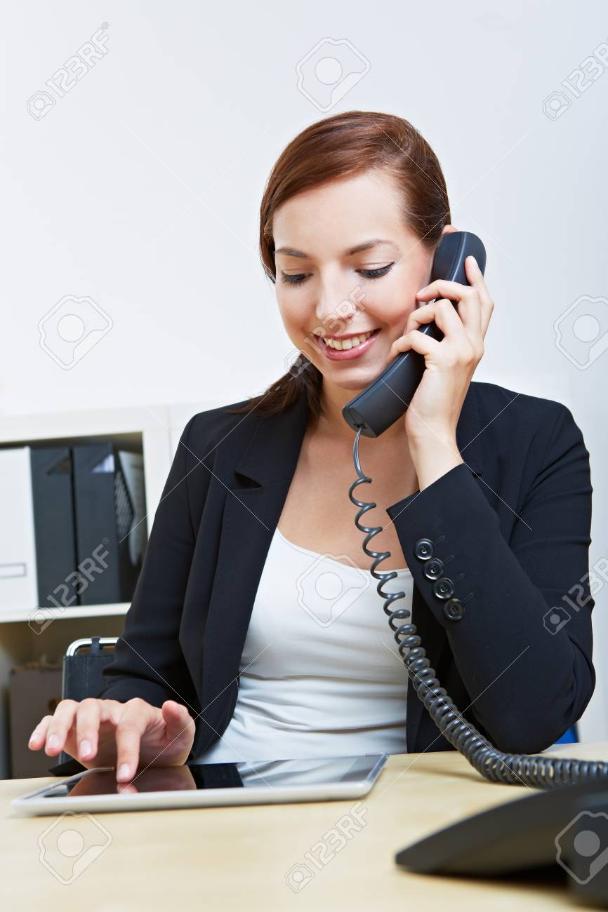 Business woman with tablet pc in her office making a phone call