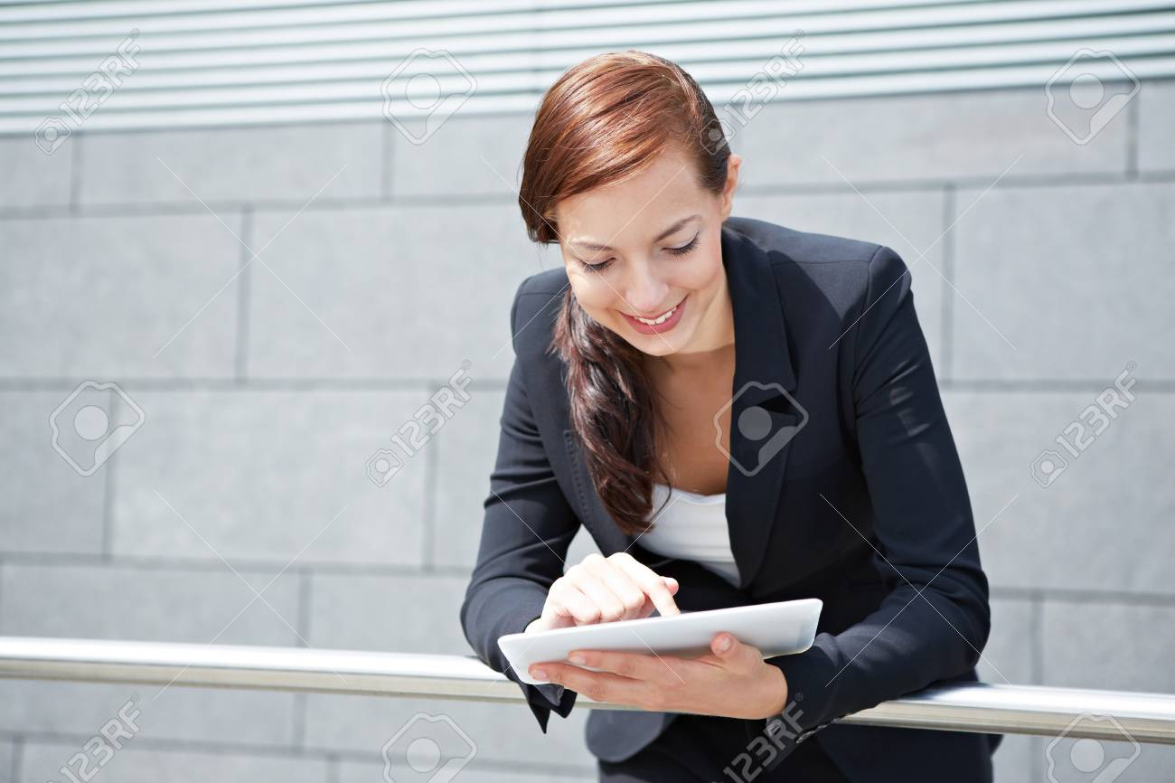 Attractive smiling businesswoman with tablet computer on the way Stock Photo - 14961881
