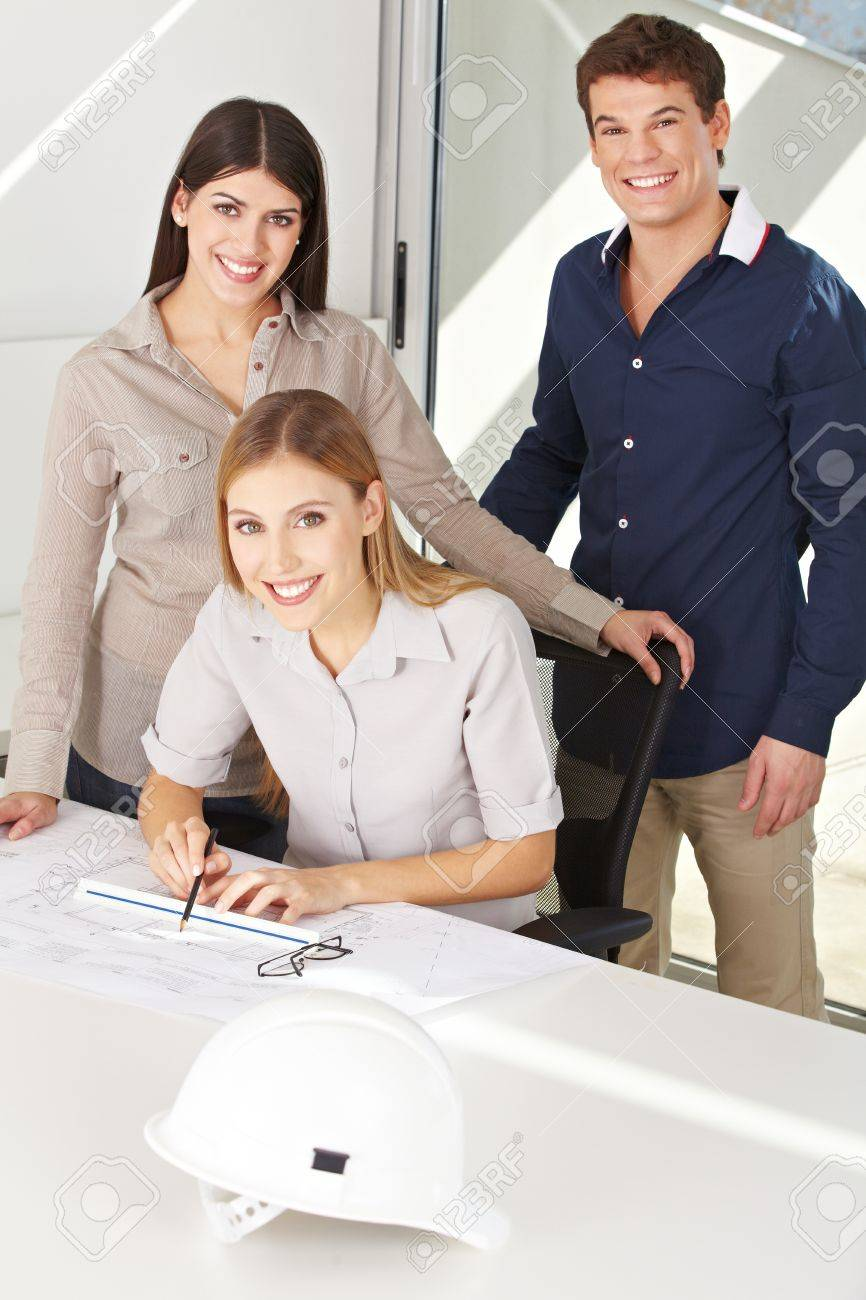 Three happy architects with construction drawing in their office Stock Photo - 15459238