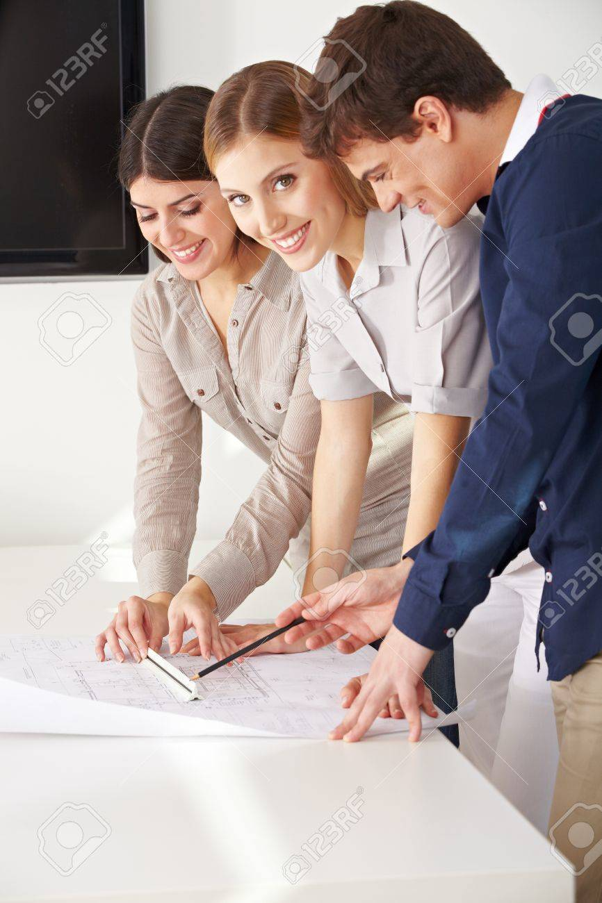 Three smiling architects working with a blueprint in their office Stock Photo - 15459269