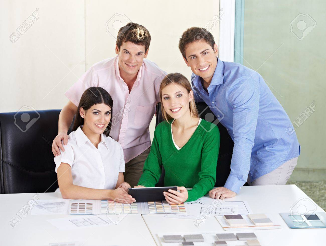 Smiling happy team of architects with tablet computer at desk Stock Photo - 15638059